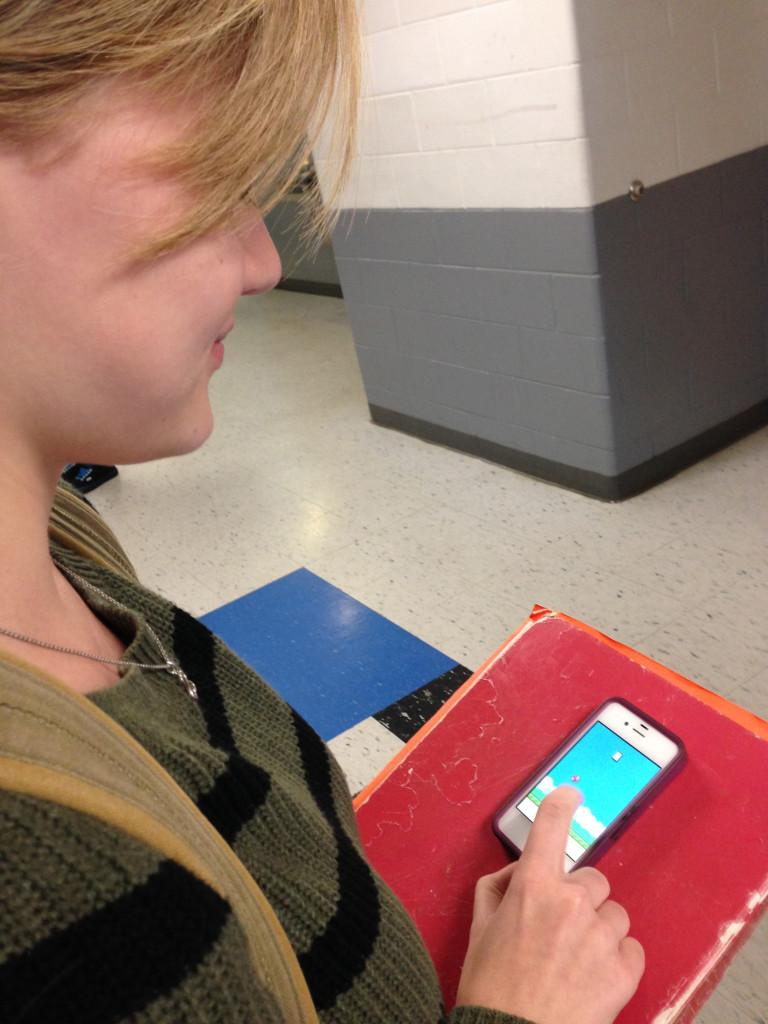 Junior Kay Hammack begins playing Flappy Bird in the hallway during break.  Many students used whatever time they had to play Flappy Bird, including during break, between classes, at lunch and in the bathroom.