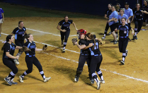 Pitcher Sam Worrell hugs catcher Alicia Tomberlin as the rest of the team runs onto the field to celebrate the regional final victory over West Orange.