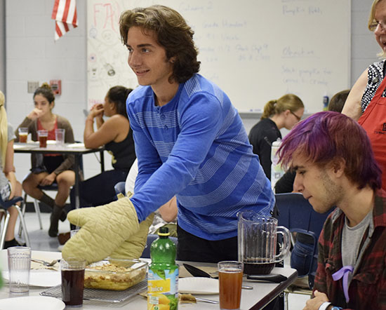 Junior Trey Hogan takes a freshly baked apple crisp to his table to serve his peers.