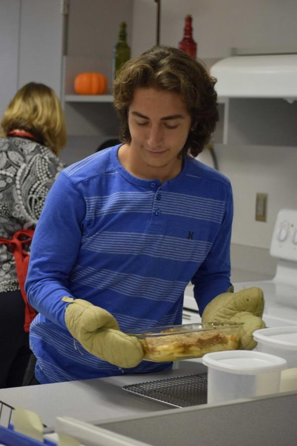 Junior Trey Hogan takes apple crisp out of the stove to cool before serving it to his peers.