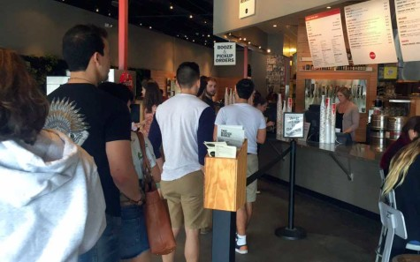 "A line gathers during lunch hour at Lazy Moon for ""Free Drink Thursdays."""
