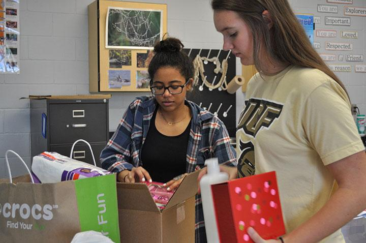 Juniors+Tatum+Annan+and+Karly+Harms+organize+the+donated+items+in+preparation+of+sending+them+off.