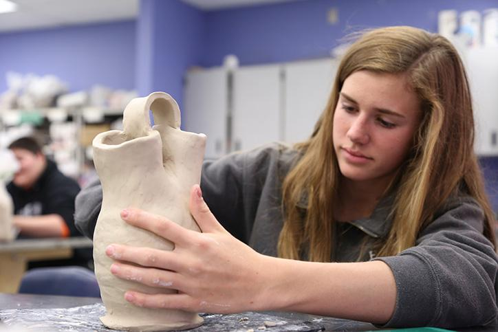 Ceramics/Pottery 1 student, freshman Julia Plescha shapes and smooths her Native American wedding vase. Plescha made the base of her vase using a pottery wheel before creating the upper part via coils.