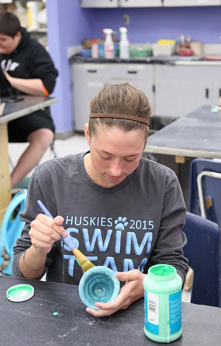 Ceramics/Pottery student, freshman Jessica Witt paints her ceramic creation.