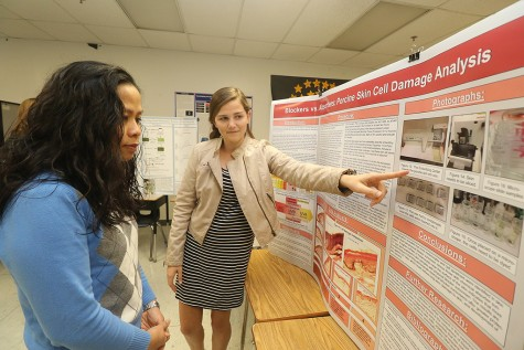 Freshman Reagan Pomp presents her project to media specialist Po Dickinson. Pomp studied the differences in chemical and physical sunscreens by testing their efficiencies on pigskin. She is one of the six girls in the experimental science class, and says the support system of women in STEM has inspired her to continue pursuing science.