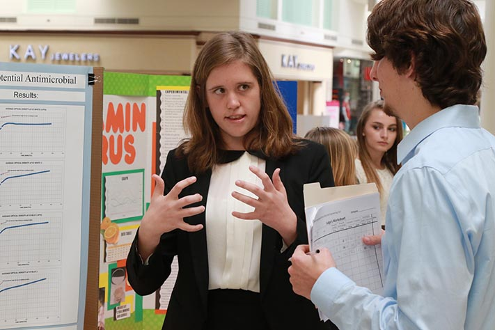 Junior Tess Marvin explains her project to a judge at the 2016 SCPS Regional Science, Math and Engineering Fair on Feb. 13. Marvin's Molecular and Cellular Biology project was judged by a variety of experts in different fields.