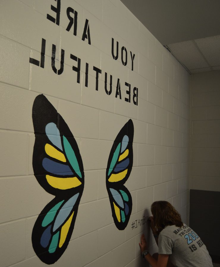 "Senior Lizzie Marvin writes ""#IAmBeautiful"" in the corner of her butterfly wing mural in the upper house girls' bathrooms.  Marvin intended for girls who take selfies with the murals to post them using the hashtag so she could see what people thought of her project."