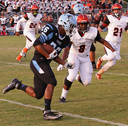 Running back Jordan Gilbert runs the ball through defenders against Oviedo on Friday, Sept. 9. The team won 17-10 with running back Tavis Thompson scoring both touchdowns.