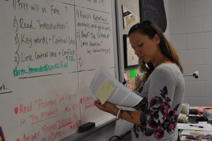 English teacher Lindsey Jackson writes the agenda for her honors classes. Every morning before school starts, Jackson organizes and makes sure all of the materials needed for class are accessible for her students.