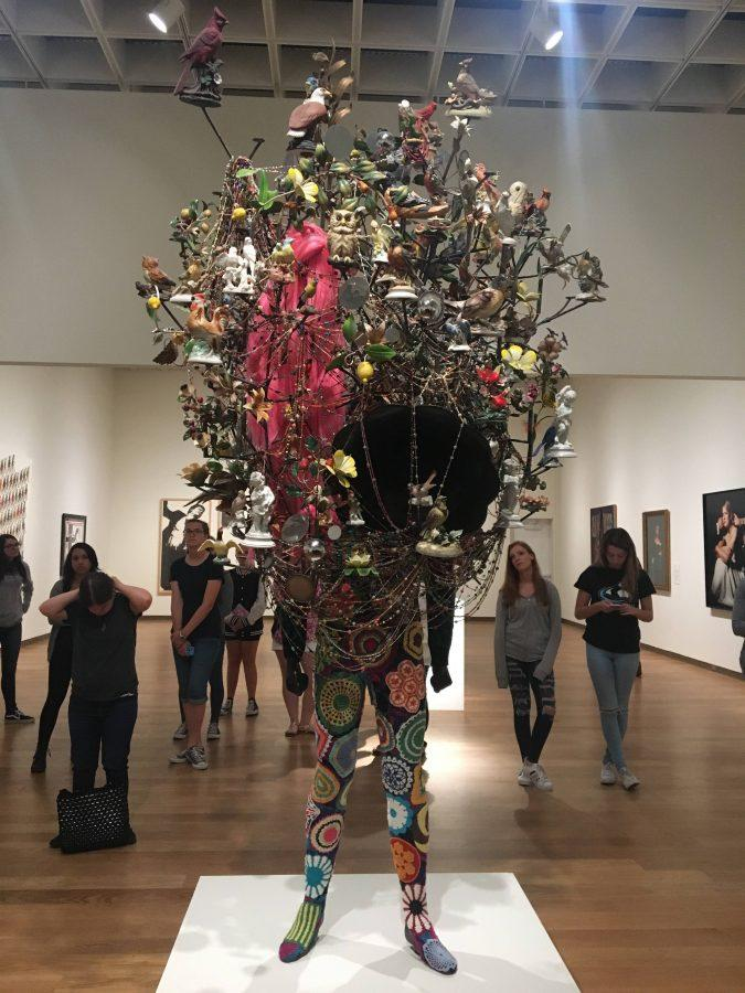 Students looking at and standing around  Soundsuit 2011, a statue made by Nick Cave on display at the Orlando Museum of Art