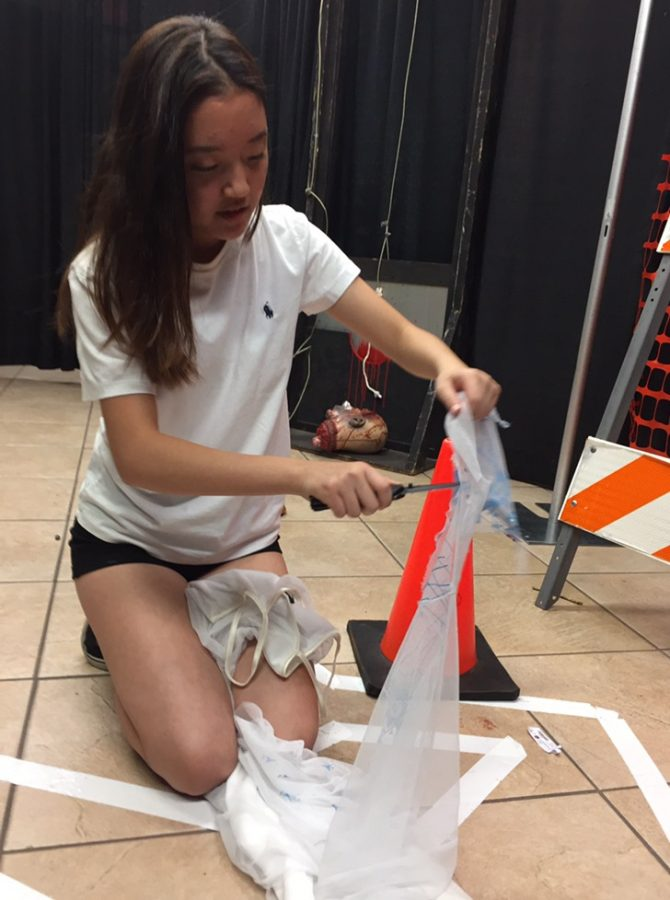 Junior Joy Yun customizes costumes for The Purge house. Volunteers were in charge of customizing their own costumes and making them fit into each of their scaring role.