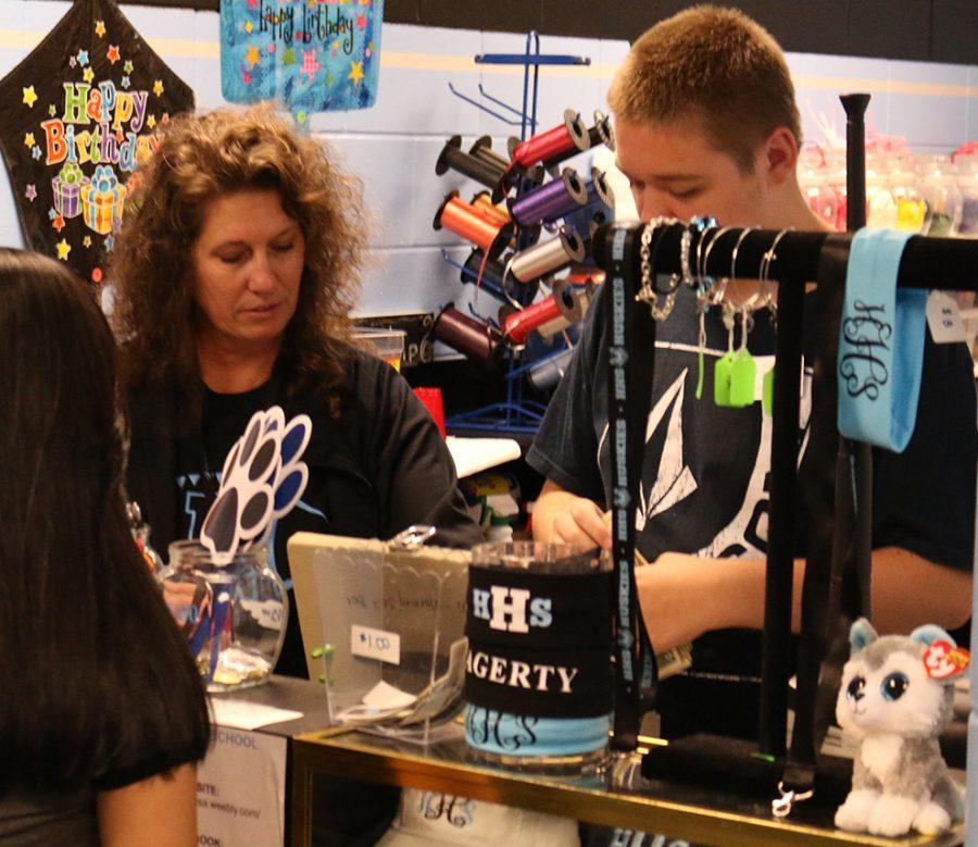 ESE teacher Tammy Harris and student Ryan Elliot run the cash register during break. Headbands are priced at $5 and the bracelets are $10.
