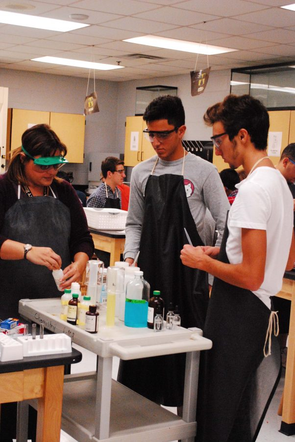 Romina Jannotti(left) helped Daniel Sanchez(middle) and Devin Bracci(right) with handling chemicals for their activity series lab.