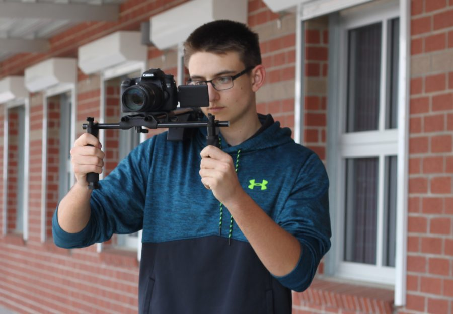 Senior Aidan Ryan gets his camera ready to film footage for his short movie. Ryan has 12 years of film experience and often asks his friends to take part in acting and producing his films.