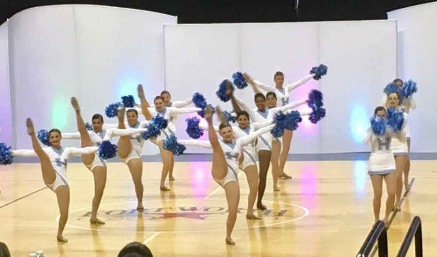 The varsity Unleashed dance team kicks high with smiles on their faces as they perform their pom dance at MA nationals.