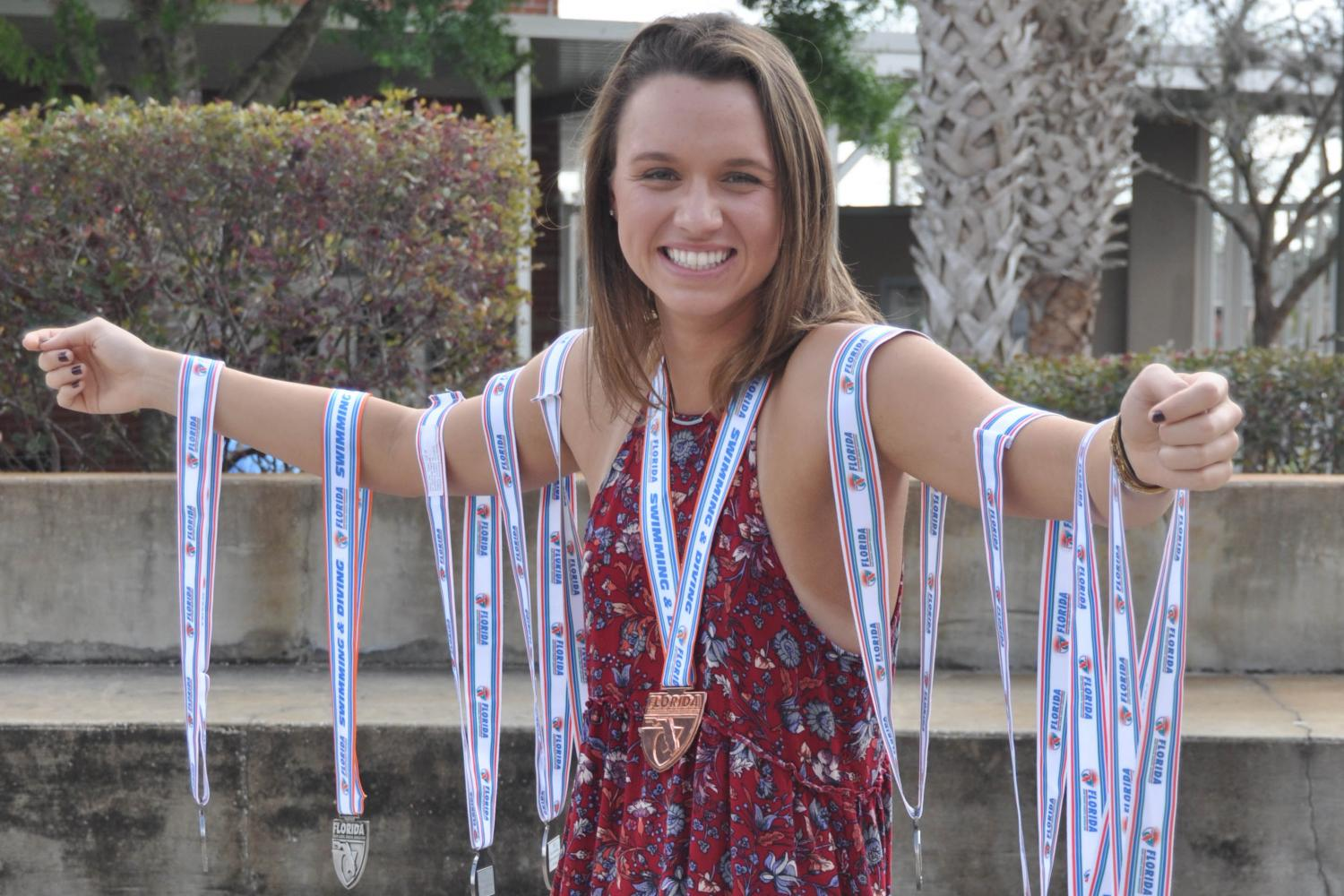 Boddiford+with+her+collection+of+medals+won+throughout+her+four+years+competing+in+high+school+swimming+tournaments.