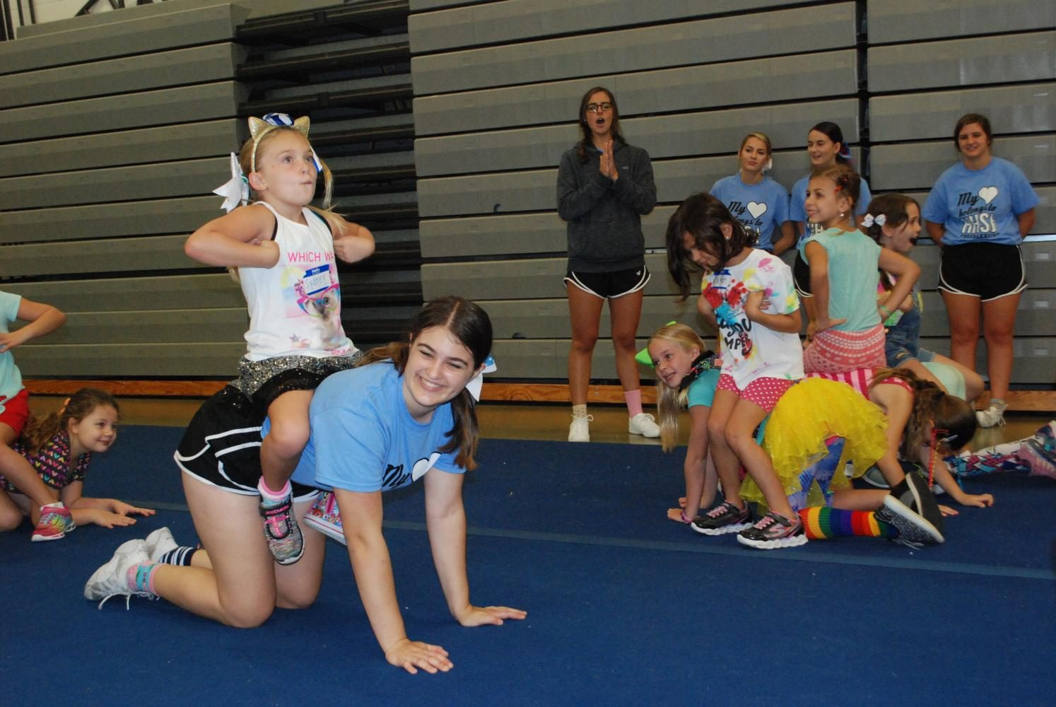 Sophomore+Annie+Tromboli+hangs+out+with+some+young+cheerleaders+during+break.+She+volunteered+this+summer+at+Hagerty%27s+Youth+Cheer+Camp.