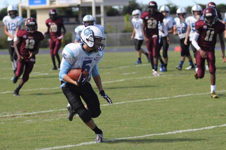 Caleb+Lowe+avoids+incoming+Wekiva+defenders+during+a+game+against+them+during+his+8th+grade+year+in+Pop+Warner+in+2014.