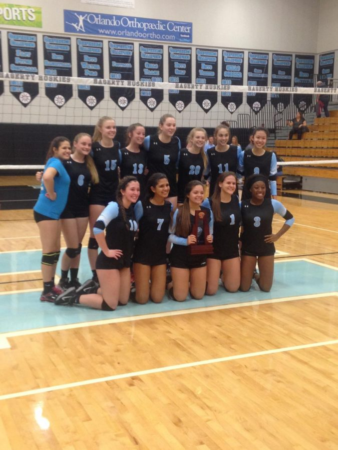 The+girls+volleyball+team+holds+the+district+championship+trophy.+The+team+defeated+Harmony+3-0+to+earn+it.