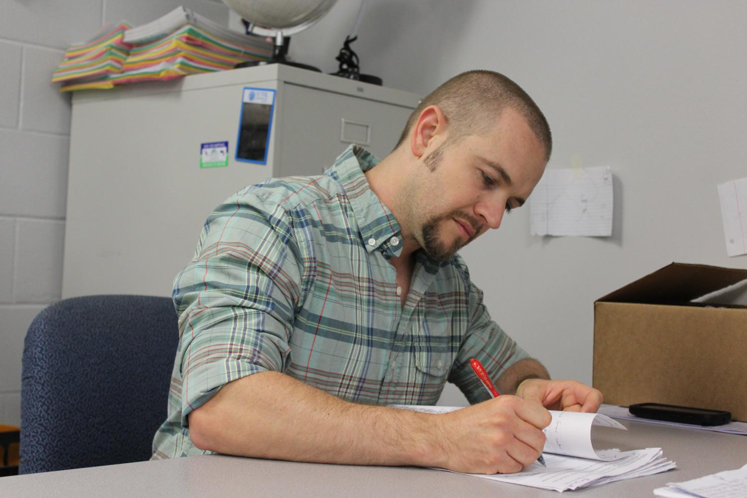Marc Pooler quietly grades papers at his desk. His hard work and outgoing personality led to his win.