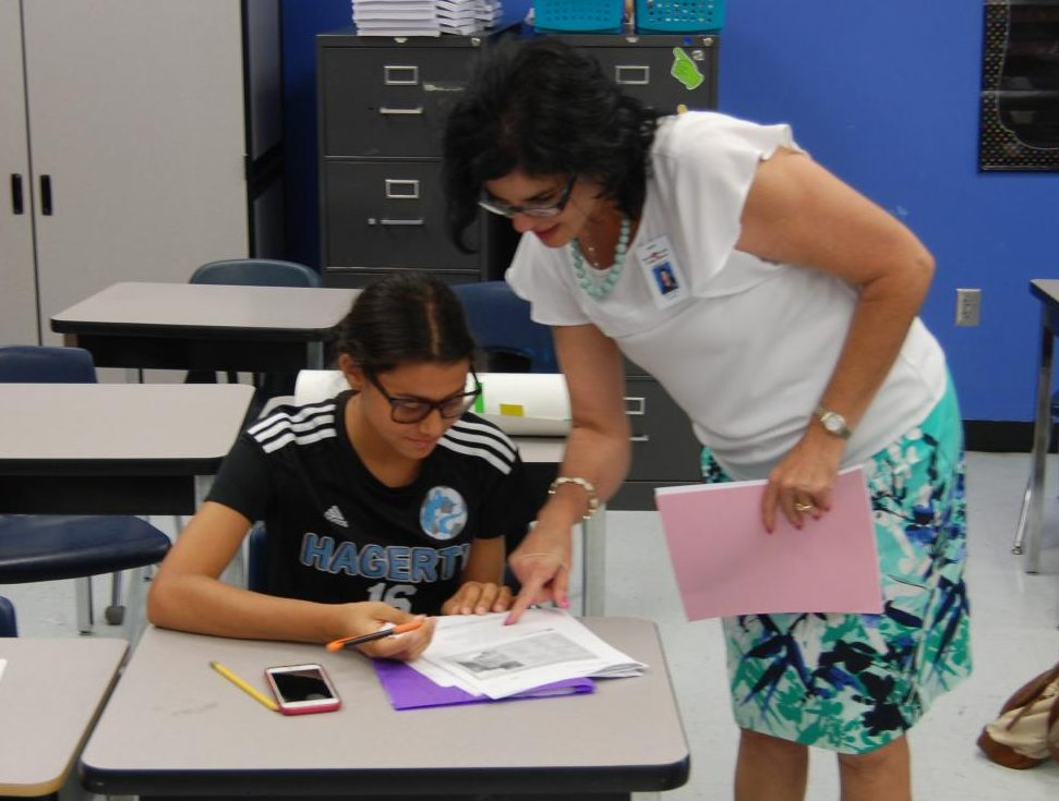 Junior Claudia Montes works on spanish assignment with spanish teacher Nitza Ariza. Montes has adapted to the change by joining clubs such as Key Club.