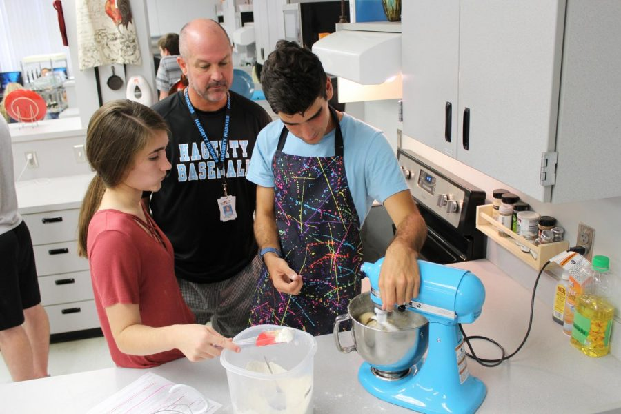 Culinary+teacher+Matthew+Thompson+supervises+while+juniors+Samantha+Gilman+and+Grant+Dettman+mix+ingredients+for+cookie+dough.+Because+of+an+increase+in+students+signing+up+for+the+class%2C+three+teachers+will+teach+culinary+next+year.