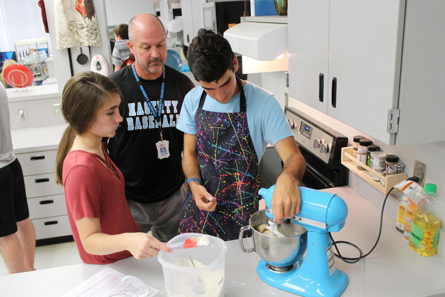 Culinary teacher Matthew Thompson supervises while juniors Samantha Gilman and Grant Dettman mix ingredients for cookie dough. Because of an increase in students signing up for the class, three teachers will teach culinary next year.