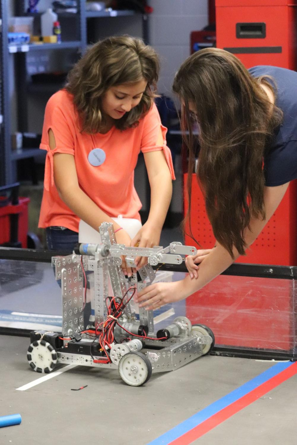 Incoming freshmen Gabriella Herrera and Falon Jones test their robot out on the field in the new robotics lab during camp.