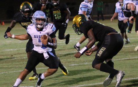 Quarterback Sammy Cordero evades Lake Minneola tacklers on one of his 20 carries. Cordero scored twice in the varsity team's 35-28 victory over Lake Minneola.
