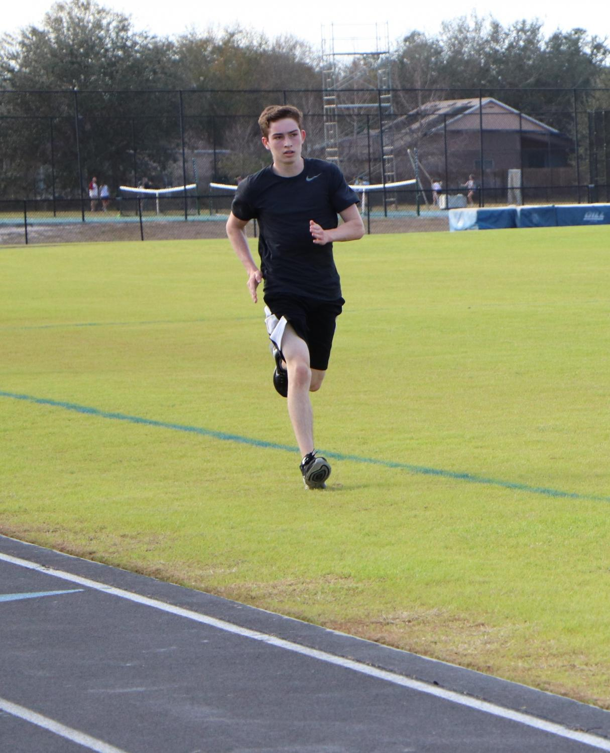 Track runner Thomas Welsh runs on the grass during track practice last year to avoid injury since the grass is not as hard as the asphalt track. The team hopes to raise enough money to get a rubber track by winter break.