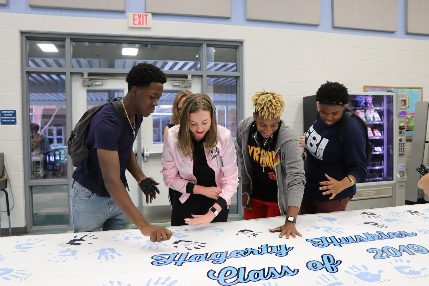 Seniors Jonathan Valentin, Katie Sherlock, Da'Zhaun Hicks and Jazmyne Essington put their painted handprint on one of the two banners for Paws on the Wall.
