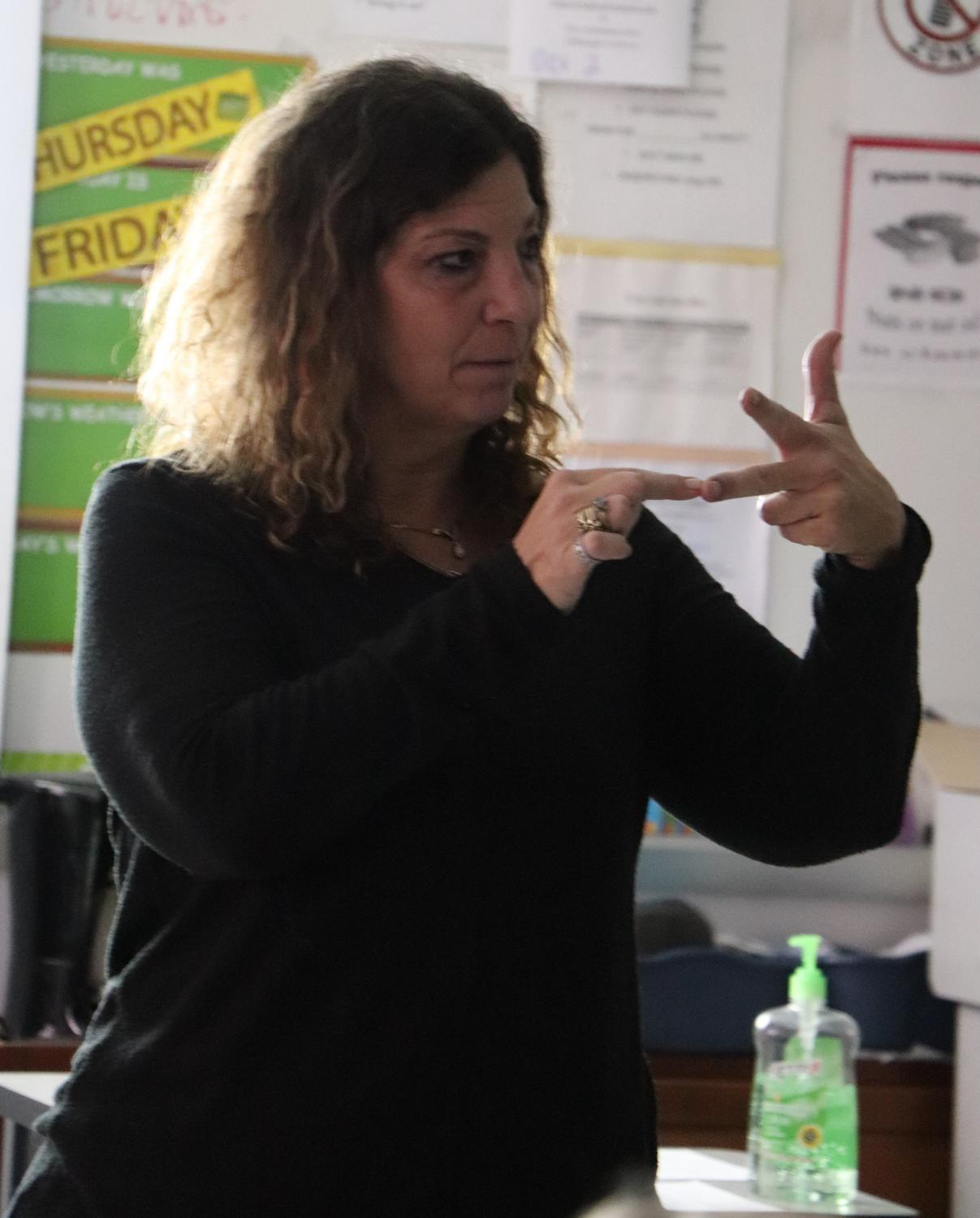 Chaves is teaching her ASL 2 class. She is showing  them how to sign a song.