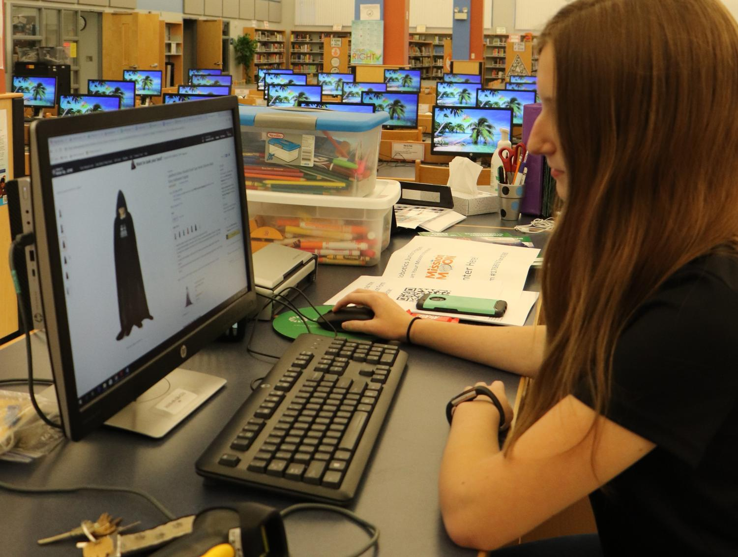 Sophomore Jolie Miller looks up capes on Amazon for the robotics team.