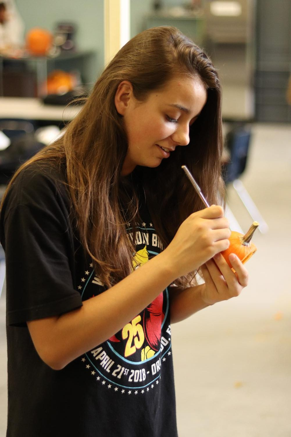 Alexis Costa carves a little pumpkin to put in her groups bigger pumpkin.