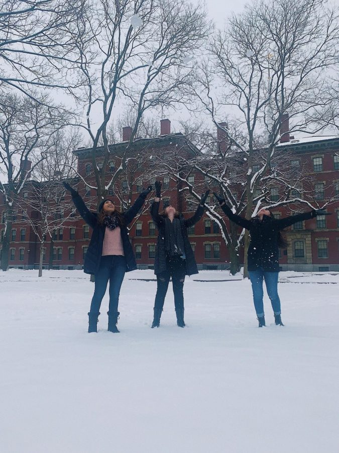 Seniors Alexis O'Brien, Sarah Gil and junior Grace Maddron play in the snow on the Harvard campus.