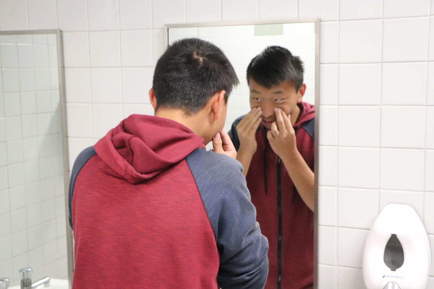 Sophomore Nicolas Cai examines his skin in the bathroom.  Cai;s daily regimen consists of a face wash in the morning.