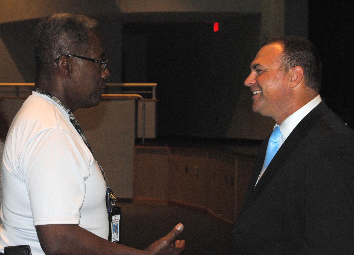 After giving an introductory speech to the faculty on Thursday, new principal Robert Frasca (right) talks with teachers, including ROTC instructor Col. Calvin Wimbish (left).