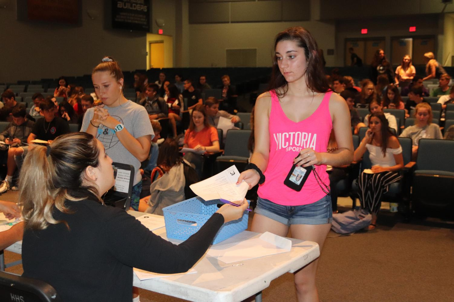Sophomores Victoria Hayward and Elaina Butler buy their parking passes in the auditorium.