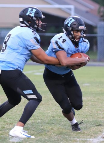 Quarterback J.J. Baird hands the ball off to running back Ethan Lopez against Gateway. The team would win 23-0.