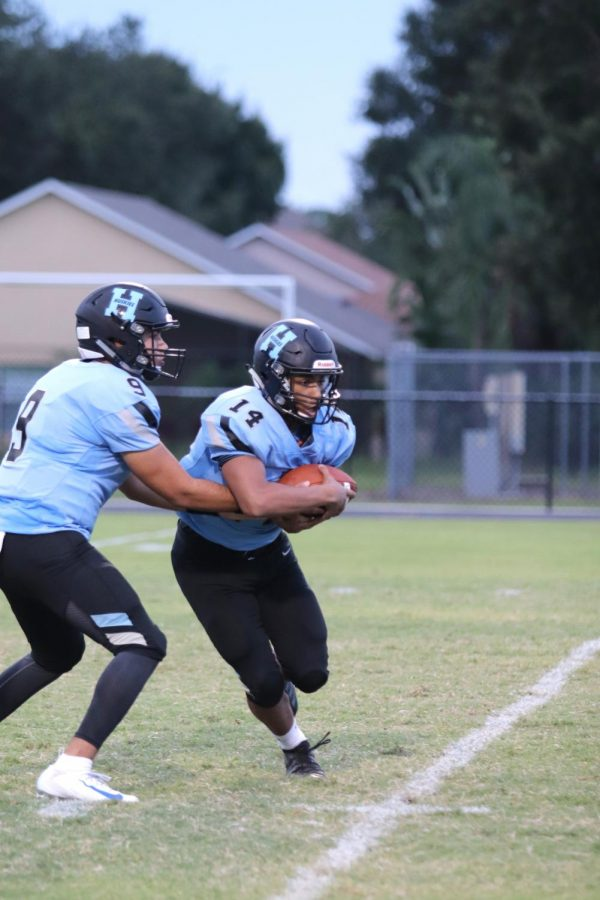 Quarterback J.J. Baird hands the ball off to running back Ethan Lopez against Gateway. The team would go on to win 23-0.