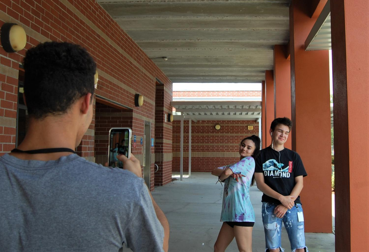 Senior Anna Cushman (middle)  makes a Tik Tok outside her 5th period with junior Sam Cosentini (right). Freshamn Schyler Arroyo (left) recorded the footage.