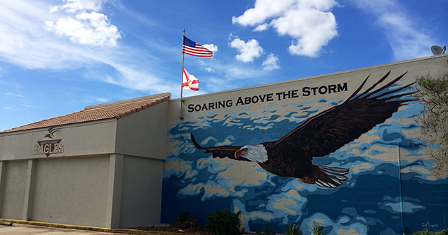 Journeys Academy mural and motto on the side of one of their outside walls.