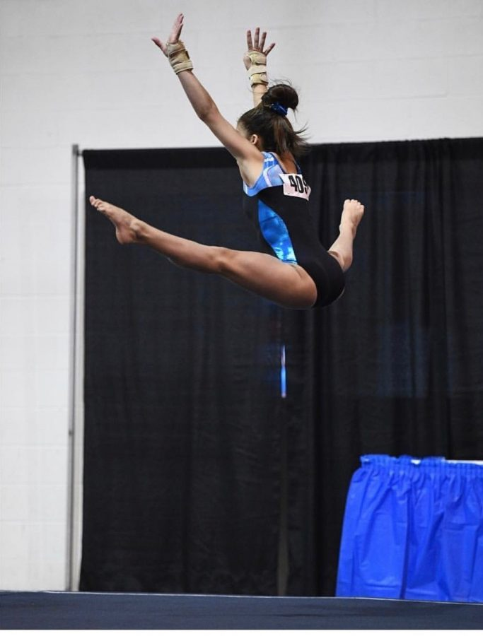 Dos Santos performing a straddle jump to finish her leap pass in her floor routine at the 2017 Junior Olympics.