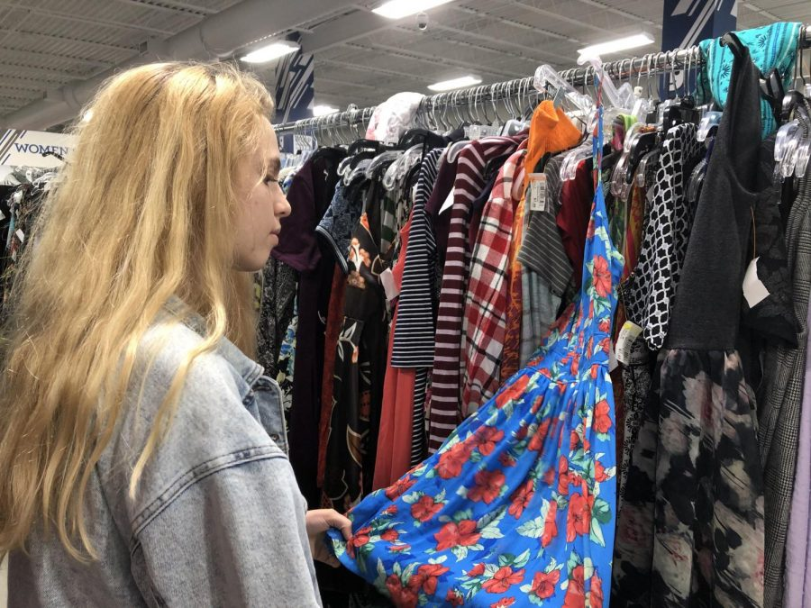 Junior Sarah Rifenberg browses through dresses at Goodwill. Many students visited similar thrift shops for cheap, trendy outfits.