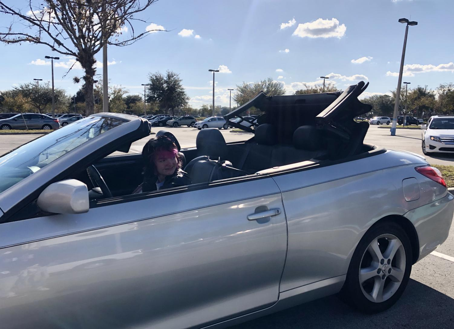 Junior Celeste Dixon takes down the roof of her convertible.  She drove it to and from school every day.