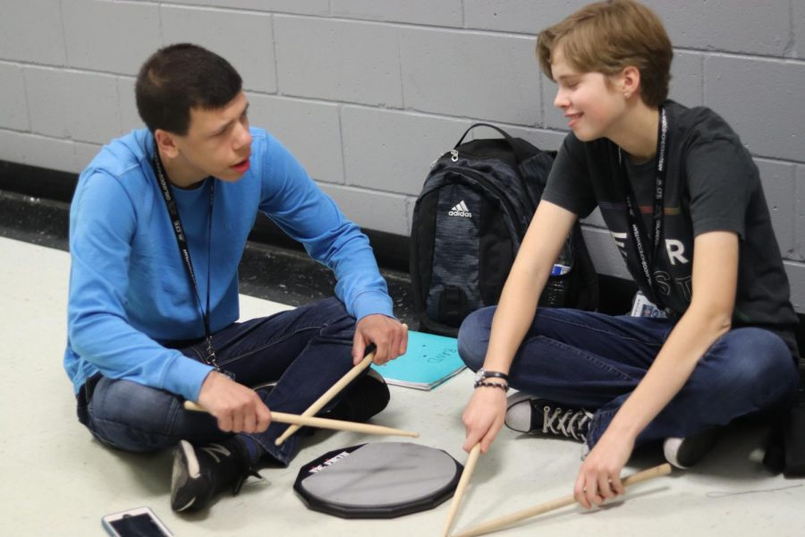 Sophomore Julia Shepp helps sophomore Jack Kimball with the drums during band.