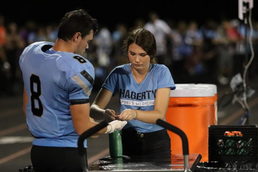 Senior Kathryn Peabody assists an athlete during a football game.