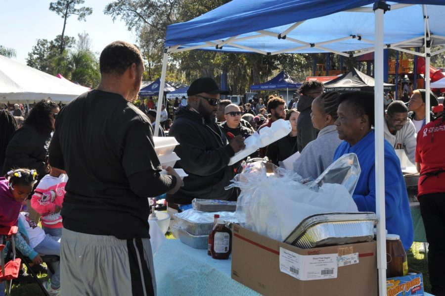Local volunteers help serve the community barbecue.