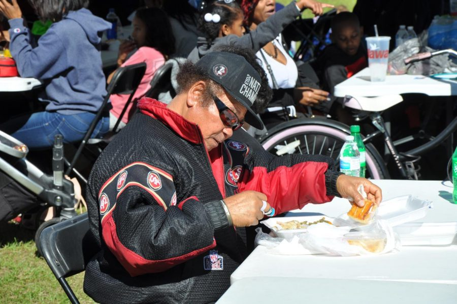 The community gathers to celebrate by eating barbecue, smoked on site at Round Lake Park.