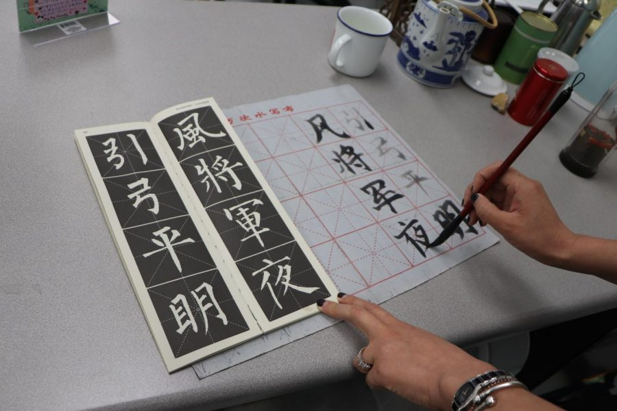 Chinese teacher Zhenzhen Zhang writes characters in Mandarin using her Mandarin kit.